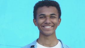 Positive African-American teen boy laughing at camera against blue background