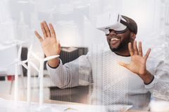 Positive African American wearing virtual reality glasses. Exciting images. Positive young African American sitting at the table while wearing virtual glasses Royalty Free Stock Photos