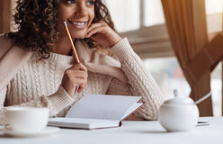 Positive African American woman making notes in the cafe. Writer creating a novel. Smiling young inspired African American woman sitting in the cafe and being Stock Photos