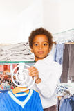 Positive African boy between rows with clothes Royalty Free Stock Photo