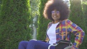 Positive afrikanische Frau mit einer Afrofrisur behindert in einem Rollstuhl, der die Kamera und das Lächeln betrachtet stock footage