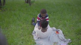Positive Afroamerikanerfrau verbreitet ihre Arme f?r Umarmungen, l?sst der Junge laufen und umarmt seine Mutter, Fall auf die Dec stock video