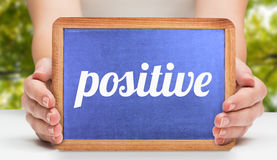 Positive against low angle view of tall trees. The word positive and hands showing chalkboard against low angle view of tall trees Stock Image
