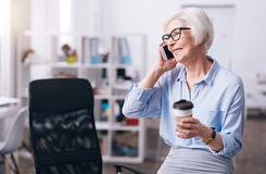 Positive aged businesswoman having a break in the office stock photography