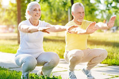 Positive aged couple doing squats in the park Stock Photo