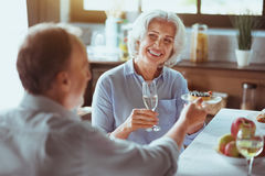 Positive aged couple enjoying festive dinenr