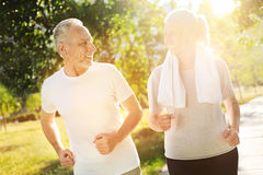 Positive aged couple jogging in the park Royalty Free Stock Images