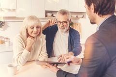Positive aged couple meeting with a real estate agent. Lookign for a new flat. Positive aged couple standing in the kitchen and looking at the tablet while Royalty Free Stock Photo
