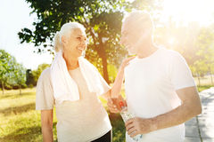 Positive aged couple resting in the park after sport activities Royalty Free Stock Photo