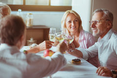 Positive aged couples drinking sparkling wine. Pleasant talks. Positive delighted aged couples sitting at the table and drinking champagne while enjoying Royalty Free Stock Photo