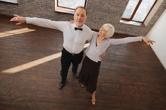 Positive aged dance couple waltzing in the dance studio Stock Photos