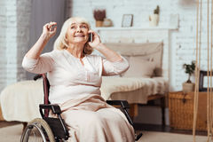 Positive aged disabled woman sitting in the wheelchair. Bright idea. Positive smiling disabled aged woman talking on cell phone and expressing joy while sitting Royalty Free Stock Photo