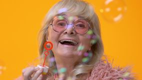Positive aged female blowing soap bubbles, feeling young, celebrating party stock video footage