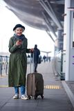 Positive aged lady is holding mobile phone with smile. Interesting news. Full length of cheerful elegant old woman resting on suitcase while standing outdoors Royalty Free Stock Photos