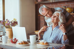 Positive aged lovign couple resting in the kitchen Stock Photos