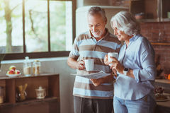 Positive aged loving couple reading newspaper stock image