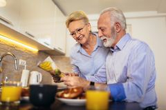Aged loving couple reading newspaper at home stock images