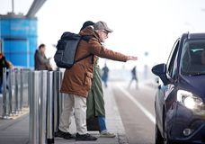 Positive aged male and female are catching taxi. Need transport. Full length e view of senior couple is standing near road. Profile of positive bearded old men Stock Image