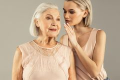 Positive aged woman being in a good mood. Something positive. Positive aged women smiling while listening to her daughters whisper stock image