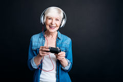 Positive aged woman playing video games Stock Photography