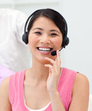 Positive Asian businesswoman talking on headset Stock Photography