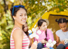 Positive Asian girl holds sticks with marshmallow Stock Photography