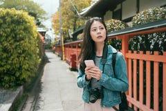 Positive asian girl traveler using smartphone royalty free stock image