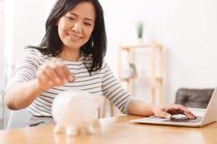 Positive asiatische Frau, die Münzen in Sparschwein setzt Stockbild