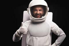 Positive astronaut is expressing gladness. I am ok. Waist up portrait of cheerful spaceman wearing helmet with full armor is standing and looking at camera with stock image