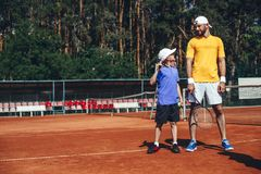 Positive athlete plying tennis with happy child. Full length side view glad little boy and beaming bearded men having fun on court outside. Satisfied guy holding Stock Photos