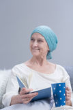 Positive attitude is the best cure!. Positive cancer woman with cancer holding book and cup, relaxing Royalty Free Stock Photos