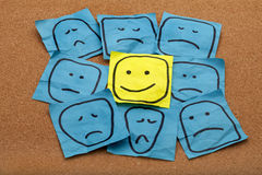 Positive attitude concept on cork board. Positive attitude or optimism concept - happy smiley face on yellow sticky note surrounded by sad unhappy blue faces Royalty Free Stock Photography
