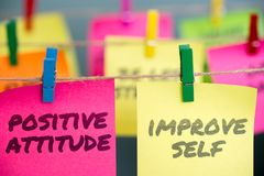 Positive Attitude And Improve Self. Written in pink and yellow sticky notes are clipped to the rope stock photo