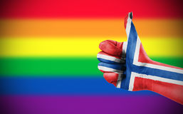 Positive attitude of Norway for LGBT community. Concept photo - Positive attitude of Norway for LGBT community. Hand against rainbow flag. Focus set on hand Royalty Free Stock Images