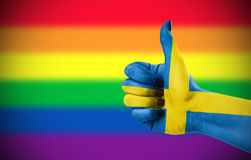 Positive attitude of Sweden for LGBT community. Concept photo - Positive attitude of Sweden for LGBT community. Hand against rainbow flag. Focus set on hand Stock Photography