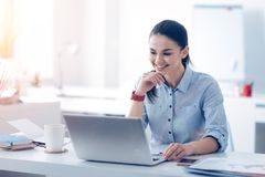 Beaming young lady looking at laptop and smiling at work Royalty Free Stock Photo