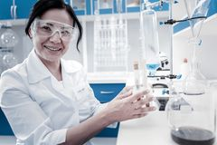Joyful female scientist smiling while holding test tubes. Positive attitude to work. Positive minded mature lady looking into the camera with a cheerful smile on royalty free stock photo