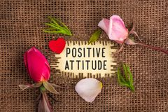 Positive attitude written in hole on the burlap. With rose flowers and wooden red heart stock images
