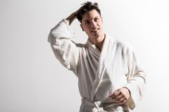 Positive attractive guy is expressing gladness. Ready to new day. Portrait of cheerful cute young man in white terrycloth bathrobe is looking forward with smile royalty free stock photography