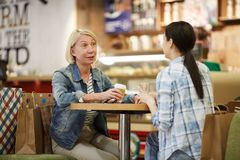 Ladies chatting over cup of coffee. Positive attractive ladies in casual clothing sitting at table and chatting over cup of coffee after shopping time in mall royalty free stock photography