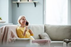 Positive lady drinking coffee at home royalty free stock photography