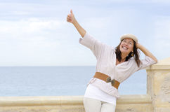 Positive attractive senior woman  outdoor. Portrait happy attractive, mature woman, positive with thumbs up and friendly smile,  with ocean and white cloudy sky Stock Photography