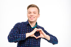 Positive attractive smiling young man showing heart made with fingers Royalty Free Stock Photography
