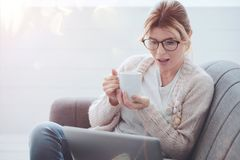 Positive attractive woman holding a cup of tea stock images