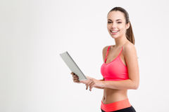 Positive attractive young fitness woman holding tablet Royalty Free Stock Image