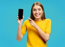 Positive attractive young girl points finger on the phone. royalty free stock images