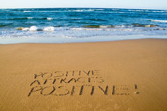 Positive attracts positive. Creative motivation concept. Positive attracts positive. Creative motivation concept written in the sand at the beach Stock Images