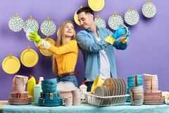 Positive awesome young man and woman looking at each other while wiping plates. Positive awesome young men and women looking at each other while wiping plates royalty free stock image