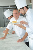 Positive baker checking finishing cake stock images