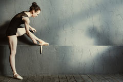 Positive ballet dancer wearing her points in the dancing saloon Stock Photos